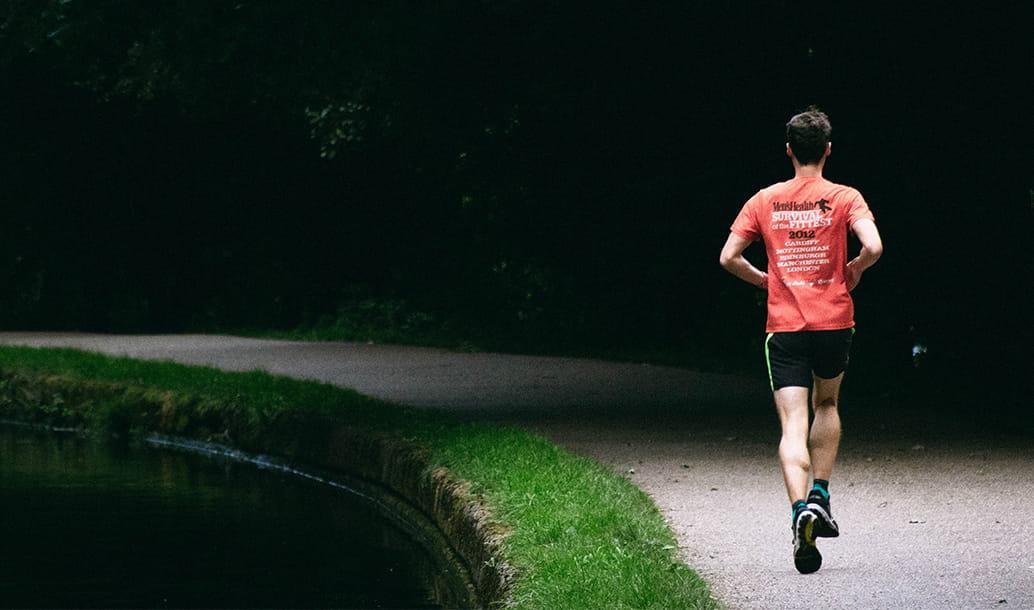 A runner runs along a London park path