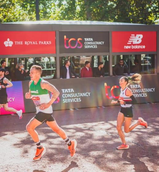 Championship runners run past the TCS hospitality area at the London Marathon