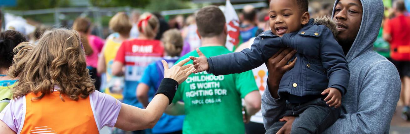 little boy high fives a Virgin Money London Marathon participant