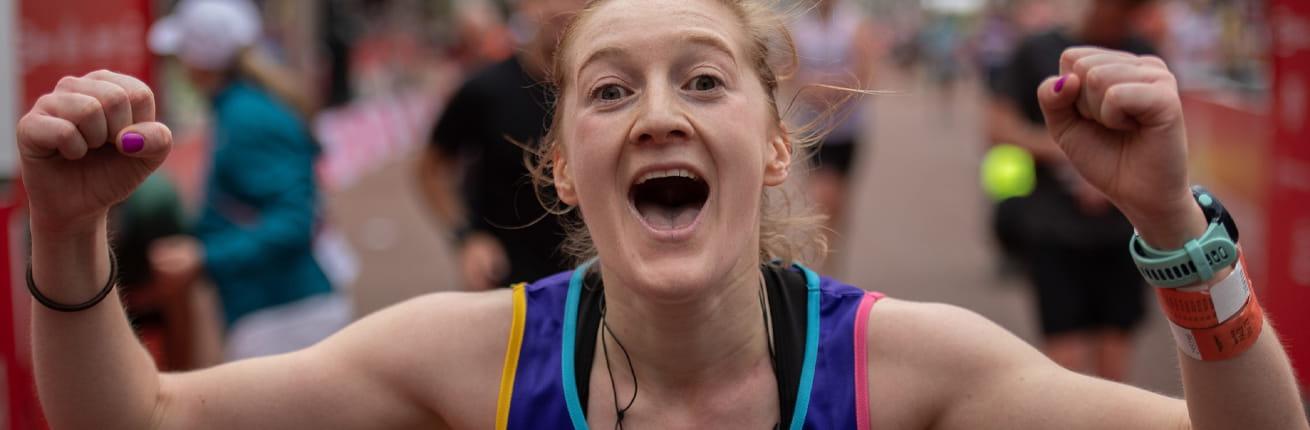 A runner celebrates after finishing the Virgin Money London Marathon